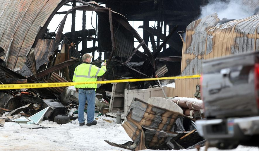 A man looks at a smoldering structure after a Sunday night fire destroyed Pat Cooper's Pine Lake Boat and Motor shop in Barry County, north of Plainwell, Mich., Monday, Feb. 9, 2015. The fire destroyed the marina and more than $250,000 in inventory. (AP Photo/Kalamazoo Gazette-MLive Media Group, Mark Bugnaski) ALL LOCAL TELEVISION OUT; LOCAL TELEVISION INTERNET OUT
