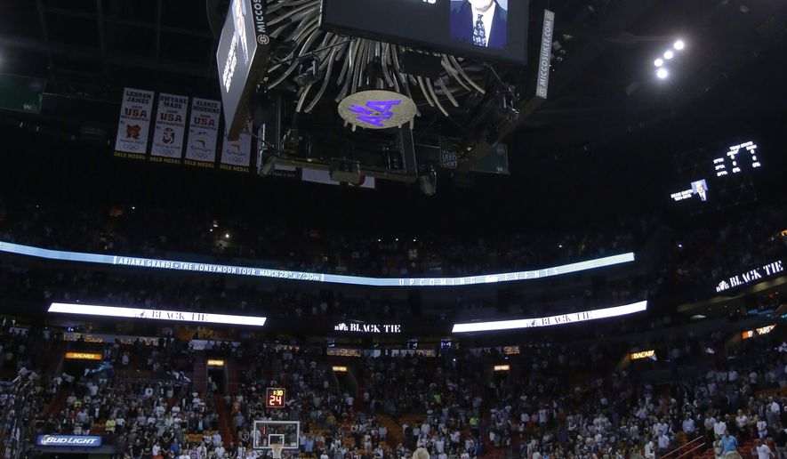 Players stand for a Moment of Silence for the late North Carolina coach Dean Smith before the start of an NBA basketball game between the Miami Heat and the New York Knicks, Monday, Feb. 9, 2015, in Miami. (AP Photo/Wilfredo Lee),