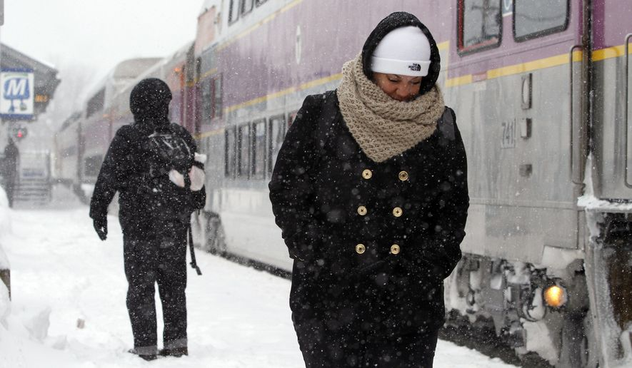 Passengers wait at the commuter rail train station Monday, Feb. 9, 2015, in Framingham, Mass. New England and portions of New York state awoke Monday to a fresh blanket of snow as a storm threatening to bring up to 1 to 2 feet to some areas churned across the Northeast, making for a slippery, tedious commute to start the workweek. (AP Photo/Bill Sikes)