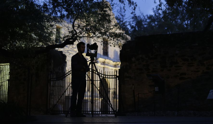 FILE - In this Jan. 9, 2014 file photo, Soheil Hamideh is silhouetted against the Alamo as he uses a camera to record images of the Alamo long barracks in San Antonio. A study by a team of Texas A&M-led architecture researchers employing lasers and digital images shows the iconic west facade of the Alamo in downtown San Antonio is slowly eroding. (AP Photo/Eric Gay, File)