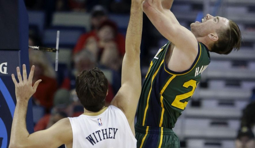 Utah Jazz forward Gordon Hayward, right, shoots against New Orleans Pelicans center Jeff Withey (5) in the first half of an NBA basketball game in New Orleans, Monday, Feb. 9, 2015. (AP Photo/Gerald Herbert)