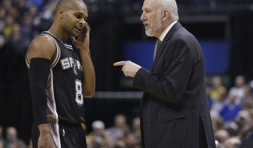 San Antonio Spurs head coach Gregg Popovich talks with Patty Mills (8) during the first half of an NBA basketball game against the Indiana Pacers, Monday, Feb. 9, 2015, in Indianapolis. (AP Photo/Darron Cummings)