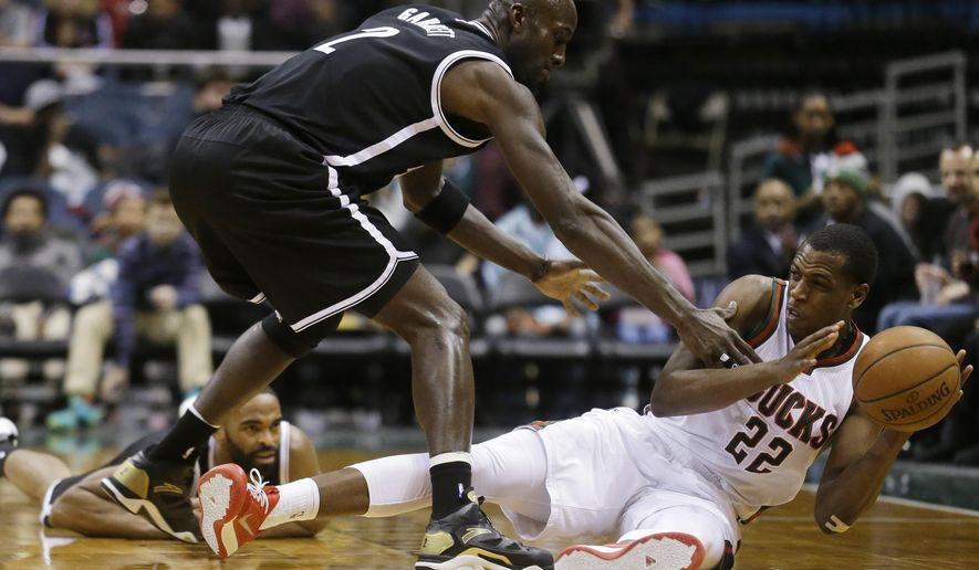 Milwaukee Bucks' Khris Middleton (22) tries to pass the ball with Brooklyn Nets' Kevin Garnett (2) defending during the second half of an NBA basketball game Monday, Feb. 9, 2015, in Milwaukee. (AP Photo/Morry Gash)