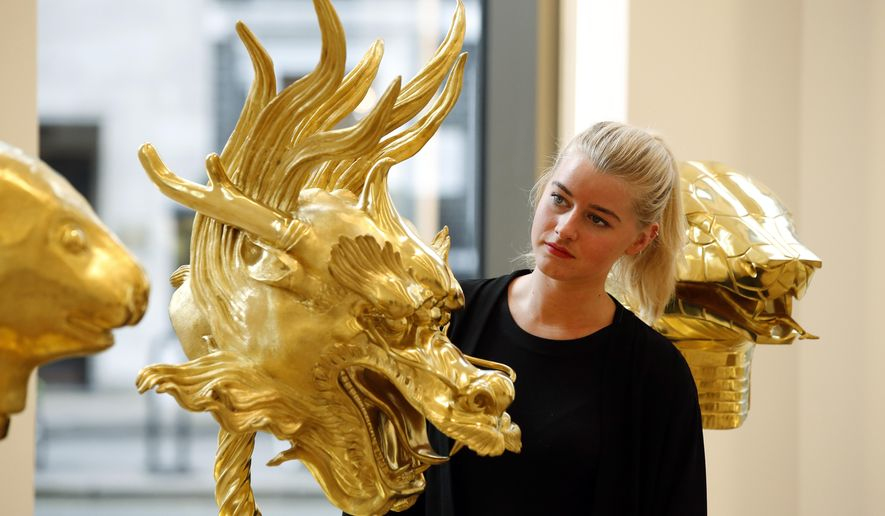 An auction house employee poses for the photographers in front of a gold plated zodiac dragon head, part of the 2010 art piece by Chinese artist Ai Weiwei, entitled: 'Circle of Animals/ Zodiac Heads', during a photo call in central London, Monday, Feb. 9, 2015. According to Phillips auction house, the zodiac heads are inspired by those which once comprised a water clock-fountain at the Old Summer Palace, the celebrated masterpiece of Chinese landscape design. The heads, each representing a sign of the Chinese Zodiac, are expected to set a record price for the contemporary artist of some 2-3 million British pounds (some 3-4,5 million US dollars, some 2,6-4,03 million euros) when offered at auction on Feb. 12-13, 2015. (AP Photo/Lefteris Pitarakis)