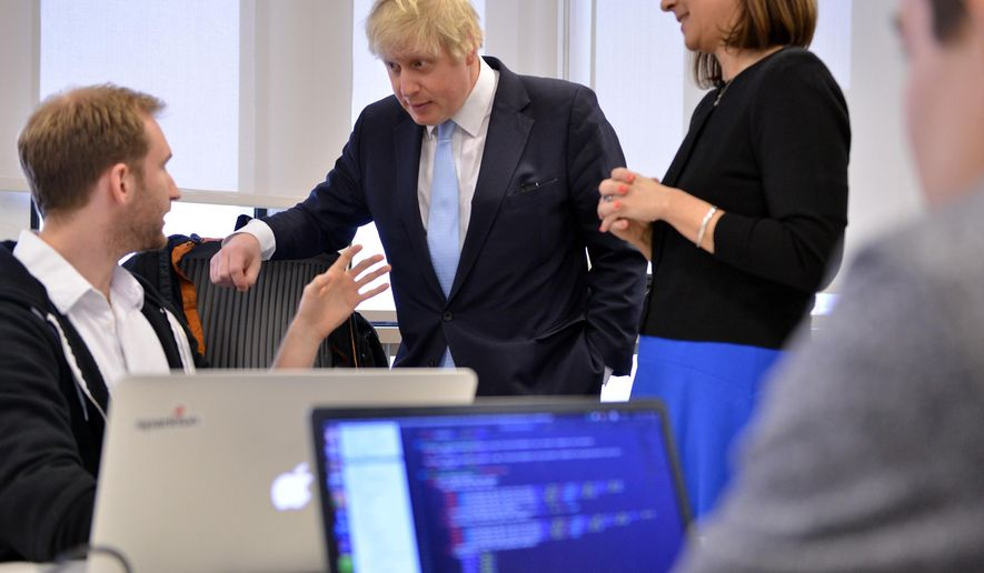 London Mayor Boris Johnson, center, speaks with Will Drevo, CEO of pharmaceutical analytics company Datasight, left, and Professor Fiona Murray, right, at the Innovation Initiative Center at the Massachusetts Institute of Technology, Monday, Feb. 9, 2015, in Cambridge, Mass. Johnson is on a six-day trade mission to the U.S., including stops in New York and Washington. (AP Photo/Josh Reynolds)