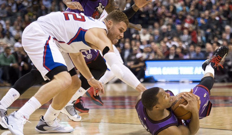 Toronto Raptors guard Kyle Lowry, right, battles for the ball against Los Angeles Clippers forward Blake Griffin, left, during the second half on an NBA basketball game, Friday, Feb. 6, 2015 in Toronto. (AP Photo/Canadian Press, Nathan Denette)