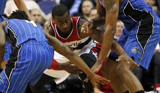 Washington Wizards guard John Wall (2) has trouble controlling the ball as Orlando Magic guard Elfrid Payton (4) and forward Channing Frye (8) go for the steal in the first half of an NBA basketball game Monday, Feb. 9, 2015, in Washington. (AP Photo/Alex Brandon)