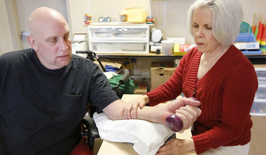 Phil Frazier recently works with Denise Fulwyler, an occupational therapist at Prosser Physical Therapy and Rehab, on Thursday Feb. 5, 2015 improving the range of motion of his left wrist. Frazier was severely injured in a 30-foot fall from a Prosser freeway overpass last October when attempted to help another motorist that had crashed. He broke his pelvis, six ribs, his left wrist and a bone in his shoulder. (AP Photo/Tri-City Herald, Bob Brawdy)