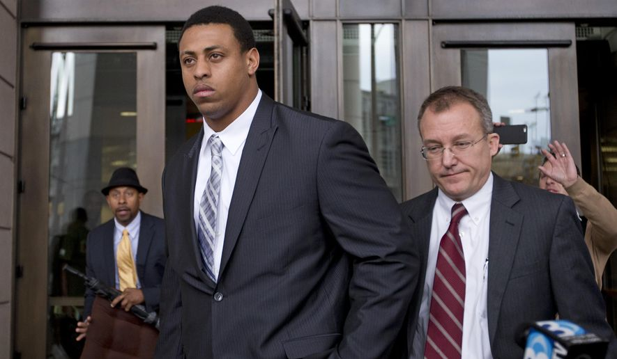 Carolina Panthers NFL football player Greg Hardy, center, leaves the Mecklenburg County Courthouse after his domestic violence charges were dismissed in Charlotte, N.C., Monday, Feb. 9, 2015. (AP Photo/Chris Keane)
