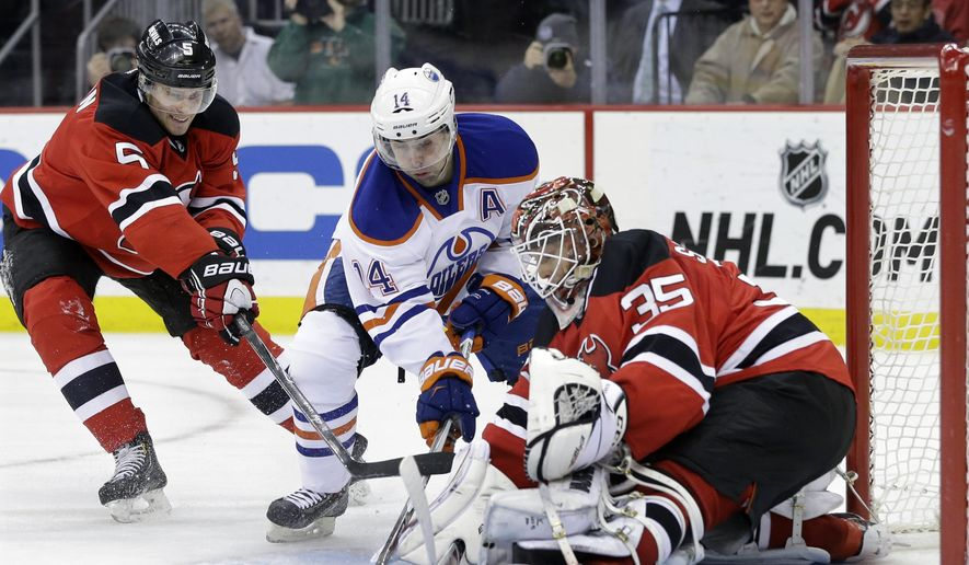 Edmonton Oilers right wing Jordan Eberle (14) tries to get the puck past New Jersey Devils defenseman Adam Larsson (5), of Sweden, and goalie Cory Schneider (35) during the first period of an NHL hockey game Monday, Feb. 9, 2015, in Newark, N.J. (AP Photo/Mel Evans)