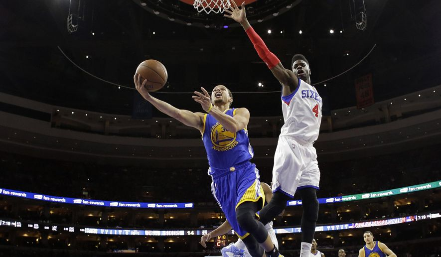Golden State Warriors' Stephen Curry (30) goes up for a shot past Philadelphia 76ers' Nerlens Noel (4) during the first half of an NBA basketball game, Monday, Feb. 9, 2015, in Philadelphia. (AP Photo/Matt Slocum)