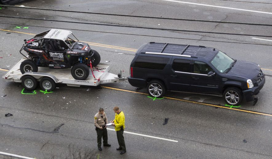 The SUV with a trailer belonging to Bruce Jenner is seen at the scene of a car crash where one person was killed and at least seven other's were injured, Saturday, Feb. 7, 2015. Olympic gold medalist Jenner was in one of the cars involved in the four-vehicle crash on the Pacific Coast Highway in Malibu, Calif., that killed a woman, Los Angeles County authorities said. (AP Photo/Ringo H.W. Chiu)