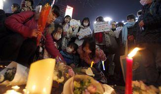 In this Sunday, Feb. 8, 2015, file photo, people gather to mourn two Japanese hostages, Kenji Goto and Haruna Yukawa, who were killed by the Islamic State group, in Tokyo. (AP Photo/Shizuo Kambayashi)