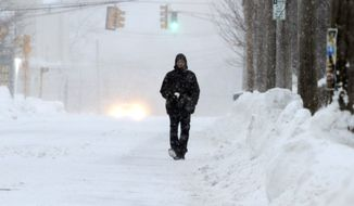 Mike Graham walks on a snow-covered street, Monday, Feb. 9, 2015, in Marlborough, Mass. New England and portions of New York state awoke Monday to a fresh blanket of snow as a storm threatening to bring up to 1 to 2 feet to some areas churned across the Northeast, making for a slippery, tedious commute to start the workweek. (AP Photo/Bill Sikes)