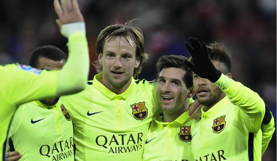 FC Barcelona's Lionel Messi of Argentina, second right, celebrates scoring his second and the fifth goal  of the match against Athletic Bilbao with teammates during their La Liga soccer match, at San Mames stadium in Bilbao, northern Spain, Sunday, Feb. 8, 2015. (AP Photo/Alvaro Barrientos)