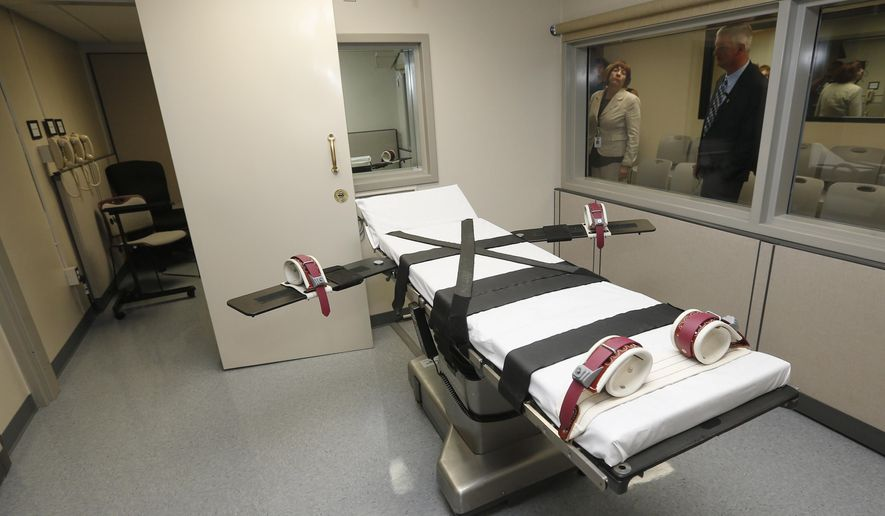 In this Oct. 9, 2014 file photo, Department of Corrections officials are pictured in the witness room at right, outside the newly renovated death chamber at the Oklahoma State Penitentiary in McAlester, Okla.  (AP Photo/Sue Ogrocki, File) **FILE**