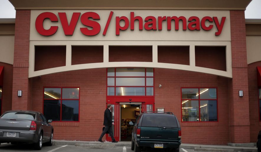 In this March 17, 2014 photo, a man walks in front of a CVS/Pharmacy in Dormont, Pa. CVS reports quarterly financial results on Tuesday, Feb. 10, 2015.  (AP Photo/Gene J. Puskar)
