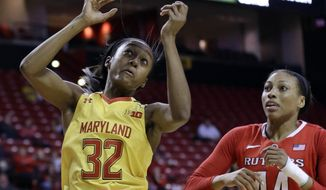 Maryland guard Shatori Walker-Kimbrough, left, reaches for a rebound in front of Rutgers' Betnijah Laney during the first half of an NCAA college basketball game, Tuesday, Feb. 10, 2015, in College Park, Md. (AP Photo/Patrick Semansky)