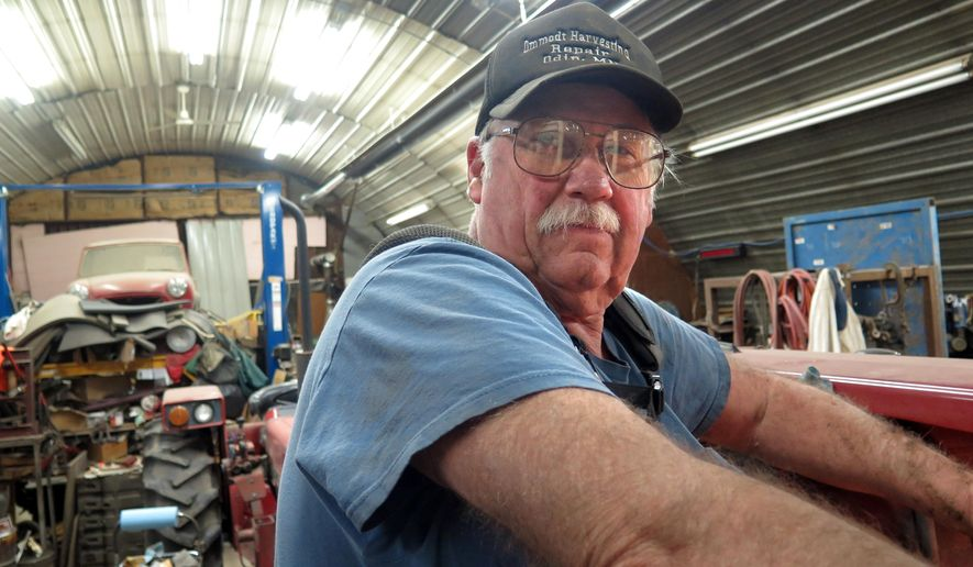Duane Ommodt works on this tractor in a shop near his farm in St. James, Minn., on Jan. 30, 2015.  Like many other Minnesota farmers, Ommodt is concerned about the upcoming crop season.  Falling corn prices have most Minnesota farmers bracing to lose money this year.  (AP Photo/Minnesota Public Radio, Mark Steil )