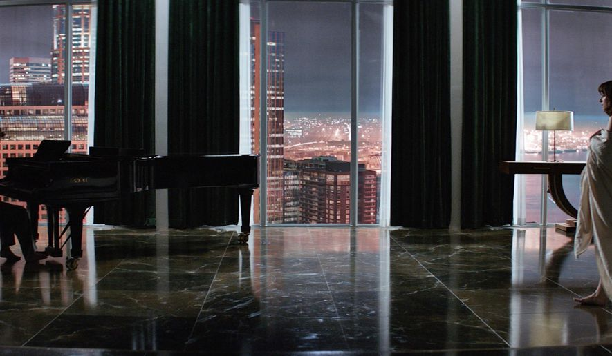 """In this image released by Universal Pictures and Focus Features, Jamie Dornan, left, and Dakota Johnson appear in a scene from """"Fifty Shades of Grey."""" (AP Photo/Universal Pictures and Focus Features)"""