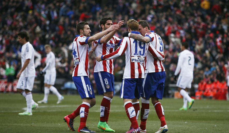 Atletico's Mario Mandzukic, right, celebrates his goal with teammates during a Spanish La Liga soccer match between Atletico Madrid and Real Madrid at the Vicente Calderon stadium in Madrid, Spain, Saturday, Feb. 7, 2015. (AP Photo/Andres Kudacki)