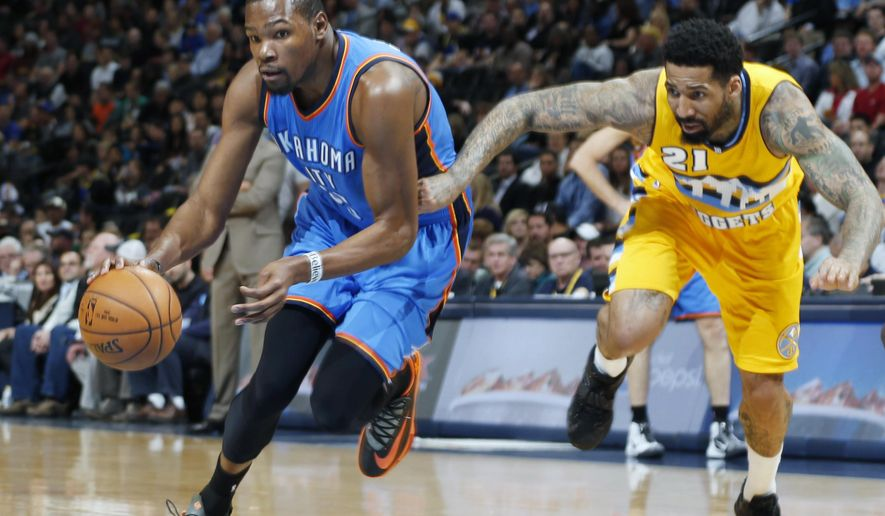 Oklahoma City Thunder forward Kevin Durant, left, drives for a shot past Denver Nuggets forward Wilosn Chandler in the first quarter of an NBA basketball game Monday, Feb. 9, 2015, in Denver. (AP Photo/David Zalubowski)