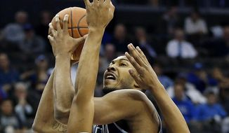 Georgetown forward Mikael Hopkins, back, goes up for a shot against Seton Hall forward Desi Rodriguez during the first half of an NCAA college basketball game, Tuesday, Feb. 10, 2015, in Newark, N.J.  (AP Photo/Julio Cortez)