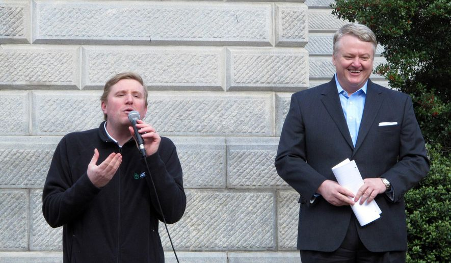 Americans for Prosperity state director Dave Schwartz, left, and South Carolina Treasurer Curtis Loftis, right, speak at a Statehouse rally against raising the gas tax on Tuesday, Feb. 10, 2015, in Columbia, S.C.  House leaders are still writing a bill to raise more money for South Carolina roads. (AP Photo/Jeffrey Collins)