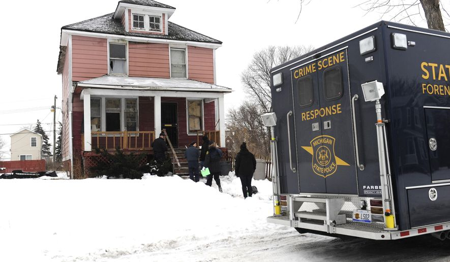A marked Michigan State Police car and forensic laboratory van sit outside the home as officers investigated a scene in Highland Park on Tuesday, Feb. 10, 2015. A Highland Park police officer was shot Monday during a raid, according to media reports. The officer, who was shot in the leg, was taken to Detroit Receiving Hospital and was expected to recover, according to WXYZ-TV. (AP Photo/The Detroit News, David Coates)