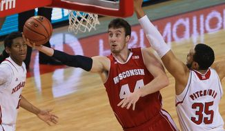 Wisconsin's Frank Kaminsky (44) goes for a layup against Nebraska's David Rivers, left, and Nebraska's Walter Pitchford (35) during the first half of an NCAA college basketball game in Lincoln, Neb., Tuesday, Feb. 10, 2015. (AP Photo/Nati Harnik)