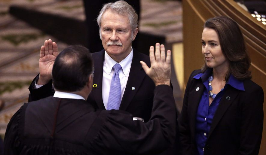 FILE - In this Jan. 12, 2015 file photo, Oregon Gov. John Kitzhaber, middle, is joined by his fiancee, Cylvia Hayes, as he is sworn in for an unprecedented fourth term by Senior Judge Paul J. De Muniz in Salem, Ore. As an ethics controversy has prompted calls for Oregon's governor to resign, the woman who would replace him has abruptly left a conference in Washington, D.C., to return home. It wasn't clear whether the unscheduled return of Oregon Secretary of State Kate Brown on Wednesday, Feb. 11, 2015, had anything to do with the influence-peddling allegations surrounding Kitzhaber's fiancee, Cylvia Hayes.  (AP Photo/Don Ryan, File)