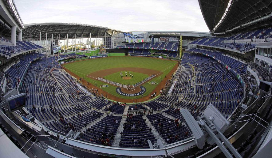 FILE - In this photo made using a fisheye lens, Teams Italy and Puerto Rico stand during the playing of the national anthems at the second-round elimination game of the World Baseball Classic at Marlins Park in Miami. A person familiar with the decision says the Marlins have been awarded the 2017 All-Star Game, and an announcement by baseball Commissioner Rob Manfred is planned for this week at the team's ballpark. (AP Photo/Wilfredo Lee, File)