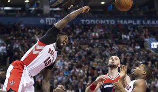 Toronto Raptors forward Amir Johnson comes down after a dunk against the Washington Wizards during the first half of an NBA basketball game Wednesday, Feb. 11, 2015, in Toronto. (AP Photo/The Canadian Press, Nathan Denette)
