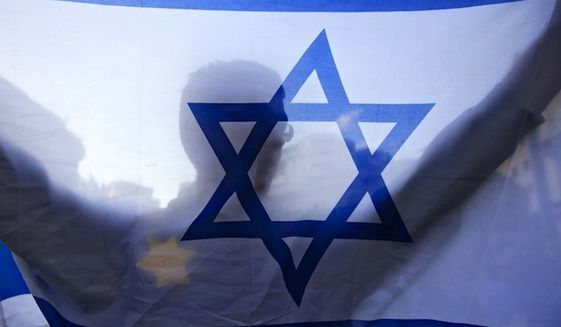 An Israeli holds a flag and wears a Star of David patch resembling the one Jews were forced to wear in Nazi Germany during a demonstration in Jerusalem. (Associated Press/Sebastian Scheiner) ** FILE **