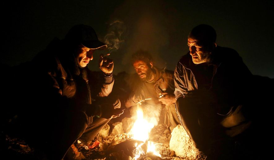 In this Wednesday, Feb. 11, 2015 photo, drug addicts gather around fire to warm themselves, in a suburb of Tehran, Iran. Anti-narcotics and medical officials say more than 2.2 million of Iran's 80 million citizens already are addicted to illegal drugs, including 1.3 million on registered treatment programs. They say the numbers keep rising annually, even though use of the death penalty against convicted smugglers has increased, too, and now accounts for more than nine of every 10 executions. (AP Photo/Ebrahim Noroozi)