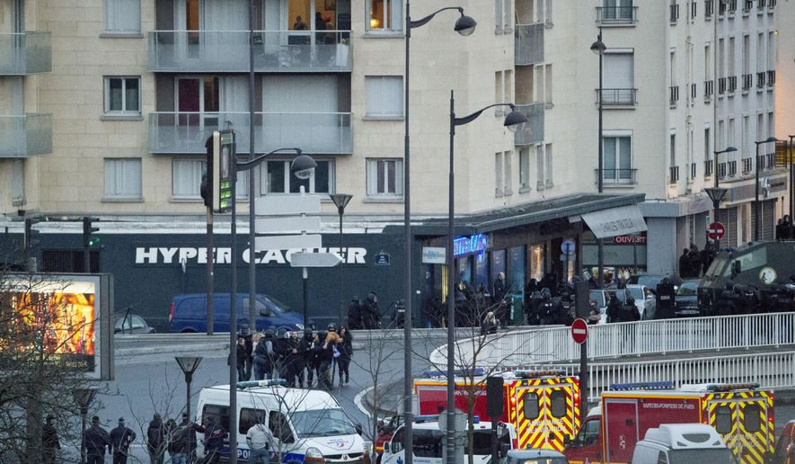 FILE - Local residents watch as police officers escort hostages after they stormed a kosher grocery in Paris, in this Friday, Jan. 9, 2015 file photo. Galvanized by the recent terror attacks in France, European Union leaders on Thursday Feb. 12, 2015 debate a range of ambitious steps to better protect their 28 nations, including exchanging airliner passenger manifests, tightening controls at the border and combating extremism on the Internet.  (AP Photo/Michel Euler)