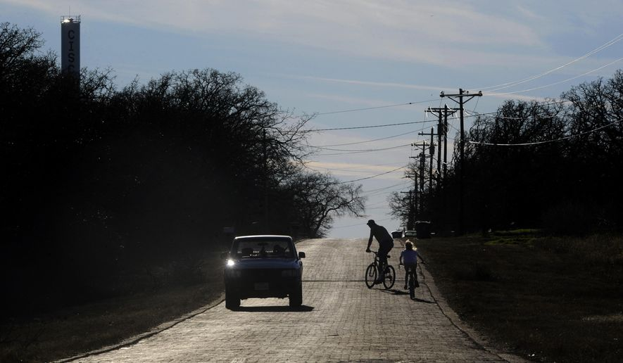 "ADVANCE FOR USE SUNDAY, FEB. 15 - In this photo taken Jan. 28, 2015, Brad Harvell watches a car pass and checks on his 7 year-old daughter Lucretia as they ride bicycles along E. 16th Street in Cisco, Texas. The brick road is one of the remains of the Bankhead Highway, the second transcontinental highway across the United States, a third of which passed through Texas and was known as ""The Broadway of America.""  (AP Photo/The Abilene Reporter-News, Ronald W. Erdrich) MANDATORY CREDIT"