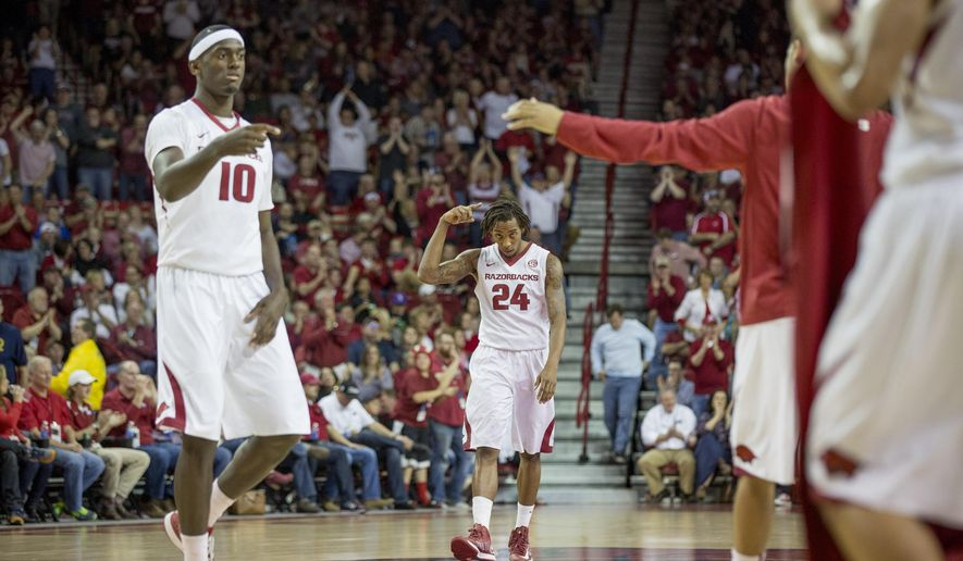Arkansas forward Bobby Portis, left, and guard Michael Qualls, center, celebrate after a 3-point basket during the second half of an NCAA college basketball game against Mississippi State, Saturday, Feb. 7, 2015, in Fayetteville, Ark. Arkansas defeated Mississippi State 61-41. (AP Photo/Gareth Patterson)