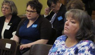 "Kathy Ostrowski, right, a lobbyist for the anti-abortion group Kansans for Life, follows a Kansas Senate committee hearing on a bill to ban a procedure described in the measure as ""dismemberment abortion,"" Thursday, Feb. 12, 2015, at the Statehouse in Topeka, Kan. To her left is Elise Higgins, a lobbyist for Planned Parenthood of Kansas and Mid-Missouri. (AP Photo/John Hanna)"
