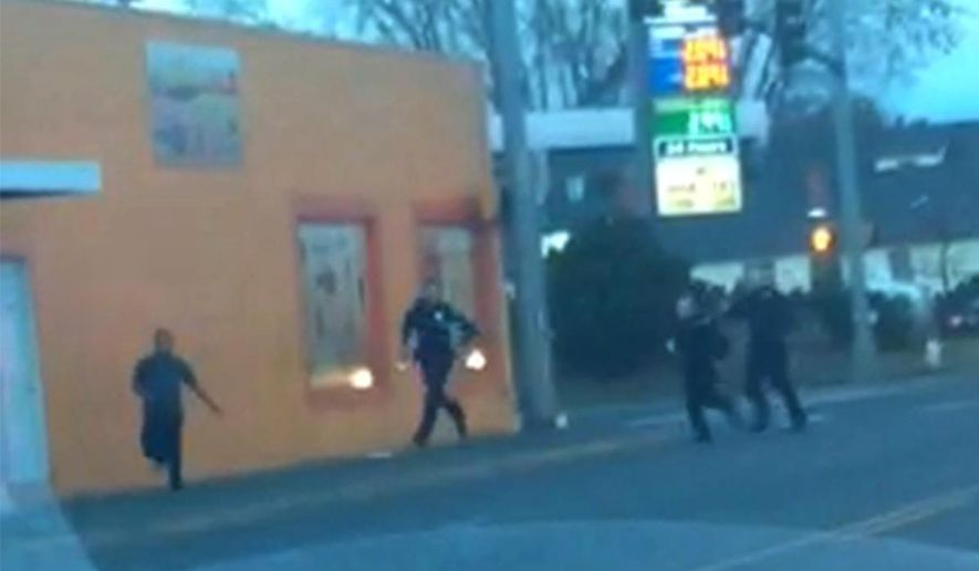 In this still frame taken from a cell phone video provided by Dario Infante and taken on Feb. 10, 2015, Antonio Zambrano-Montes, left, turns to face police officers while running from them in Pasco, Wash. Moments later, Zambrano-Montes was shot and killed. Pasco police said he threw multiple rocks, hitting two officers, and refused to put down other stones.  (AP Photo/Dario Infante)