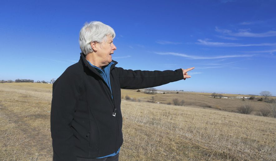 FILE- In this Jan. 16, 2015 file photo, Susan Dunavan, who opposes the Keystone XL pipeline, points to the planned route of the pipeline which will run through on her property, in York, Neb. TransCanada is temporarily suspending efforts to seize Nebraska land for the Keystone Pipeline XL amid a legal challenge. On Thursday, Feb. 12, 2015, a Holt County District judge issued a temporary injunction, keeping TransCanada from invoking eminent domain along the proposed Keystone Pipeline route in northern Nebraska. TransCanada agreed to the order, hoping to get an accelerated trial schedule. (AP Photo/Nati Harnik, file)