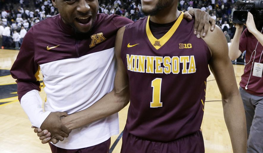 Minnesota guard Andre Hollins, right, celebrates with a teammate after an NCAA college basketball game against Iowa, Thursday, Feb. 12, 2015, in Iowa City, Iowa. Hollis scored 20 points as Minnesota won 64-59. (AP Photo/Charlie Neibergall)