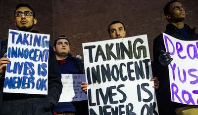 University of Michigan-Flint students, from left to right, Bilal Ali, Michael Puro, Mohamed Samman and Zafir Abutalih attend a vigil at the school on Wednesday, Feb. 11, 2015, in downtown Flint, Mich., in memory of three people who were killed Tuesday near UNC-Chapel Hill, N.C. Craig Stephen Hicks appeared in court Wednesday on charges of first-degree murder in the deaths of Deah Shaddy Barakat, his wife Yusor Mohammad and her sister Razan Mohammad Abu-Salha. (AP Photo/The Flint Journal, Jake May)