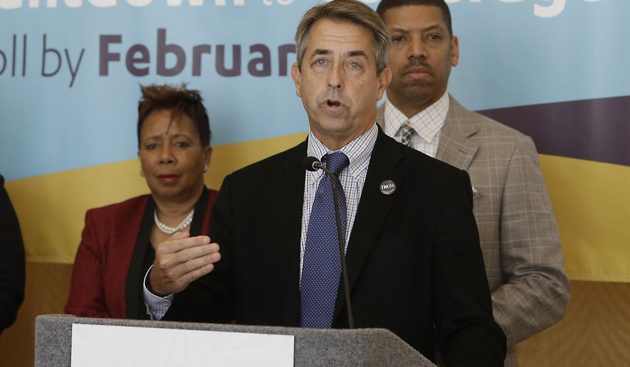 In this photo taken Feb. 9, 2015, Peter Lee,  center, executive director of Covered California, the state's health insurance marketplace, discusses health insurance sign ups at a news conference with Sacramento Mayor Kevin Johnson, right,  in Sacramento Calif.   With the open enrollment deadline Sunday, California officials said Thursday, Feb. 12,  2015, that the state is falling short of its goal to sign up 1.7  million people for private health coverage in the second year of the federal health expansion. (AP Photo/Rich Pedroncelli)
