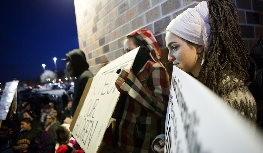 In this photo taken Tuesday, Feb. 10, 2015, Hanna Forer, 20, stands with other protestors as they listen to Native American leaders speak during an anti-racism demonstration at the Rushmore Plaza Civic Center in Rapid City, S.D. Some American Indians say racial tensions were exacerbated by reports of Native American children being subjected to racial slurs and sprayed with beer at a minor league hockey game in Rapid City in late January. A similar incident was reported during a recent stock show and rodeo at the Rushmore Plaza Civic Center. (AP Photo/Rapid City Journal, Josh Morgan) TV OUT