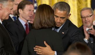 President Barack Obama hugs Susan Selke next to Richard Selke, left, the parents of Clay Hunt, after signing into law the Clay Hunt Suicide Prevention for American Veterans Act, named for Clay Hunt, which calls for evaluation of existing Veterans Affairs mental health and suicide prevention programs and expands the reach of these programs for veterans, Thursday, Feb. 12, 2015, at the White House in Washington. The bill is named for Clay Hunt of Texas, a Marine Corps combat veteran who struggled with post-traumatic stress disorder after serving in Iraq and Afghanistan and who killed himself in March 2011 at the age of 28.(AP Photo/J. Scott Applewhite)