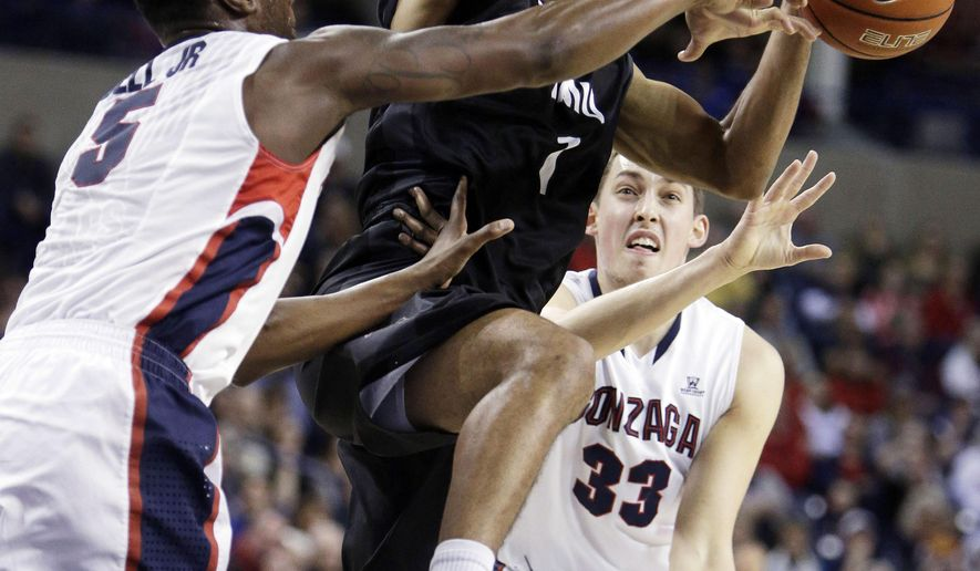 Loyola Marymount's Evan Payne, center, drives against Gonzaga's Gary Bell Jr. (5) and Kyle Wiltjer (33) during the first half of an NCAA college basketball game, Thursday, Feb. 12, 2015, in Spokane, Wash. (AP Photo/Young Kwak)