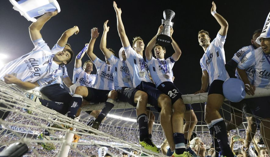 FILE - In this Dec. 14, 2014, file photo, Racing's Diego Milito, third right, lifts the trophy as he sits with other teammates on top of the goal post after winning the Argentine soccer league final match against Godoy Cruz in Buenos Aires, Argentina. Racing start its 2015 campaign against Rosario Central with Ricardo Centurion being the only change in the roster from last year's championship team. (AP Photo/Victor R. Caivano, File)