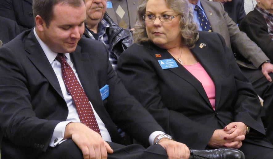 John Commerford, left, a lobbyist for the National Rifle Association, confers with Patricia Stoneking, president of the Kansas State Rifle Association, during a Kansas Senate hearing on gun-rights legislation, Thursday, Feb. 12, 2015, at the Statehouse in Topeka, Kan. The legislation would allow Kansas residents to carry concealed firearms without a state permit. (AP Photo/John Hanna)