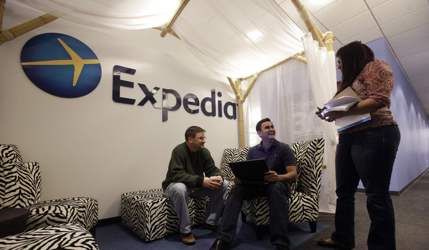 Expedia analytics team workers Mike Brown, left, Saurin Pandya and Prashanti Tata chat in an alcove set up for employees, in Bellevue, Wash., in this Jan. 15, 2015, file photo. Expedia announced on Thursday, Feb. 12, 2015, that it is buying rival online travel site Orbitz for approximately $1.33 billion. The deal comes less than a month after Expedia announced the $280 million acquisition of another rival, Travelocity. (AP Photo/Elaine Thompson, File)